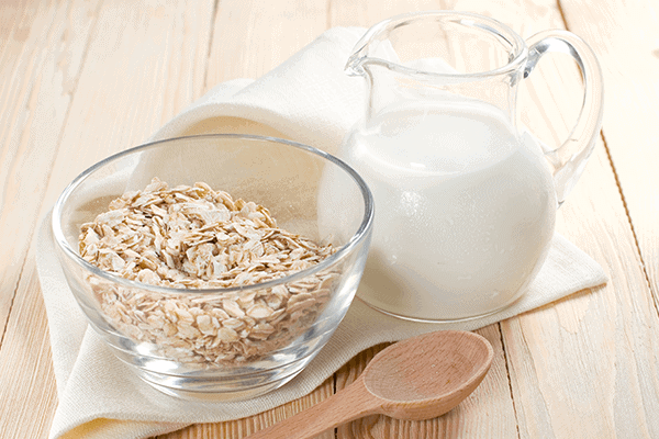 oats in a glass bowl with wooden spoon next to bowl and a large glass jug of milk