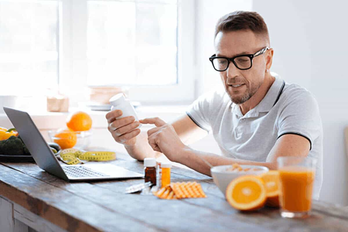 Man holding a supplement bottle and looking at more supplements