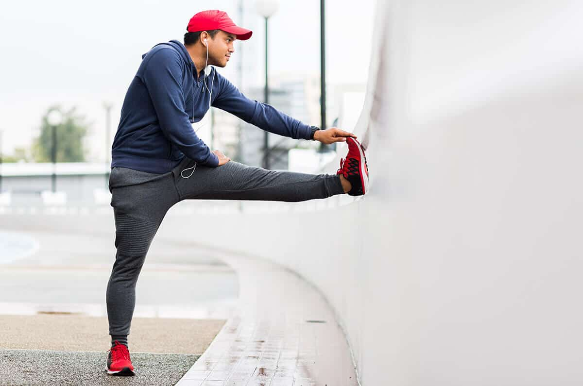 Male runner stretching on a bridge while exercising