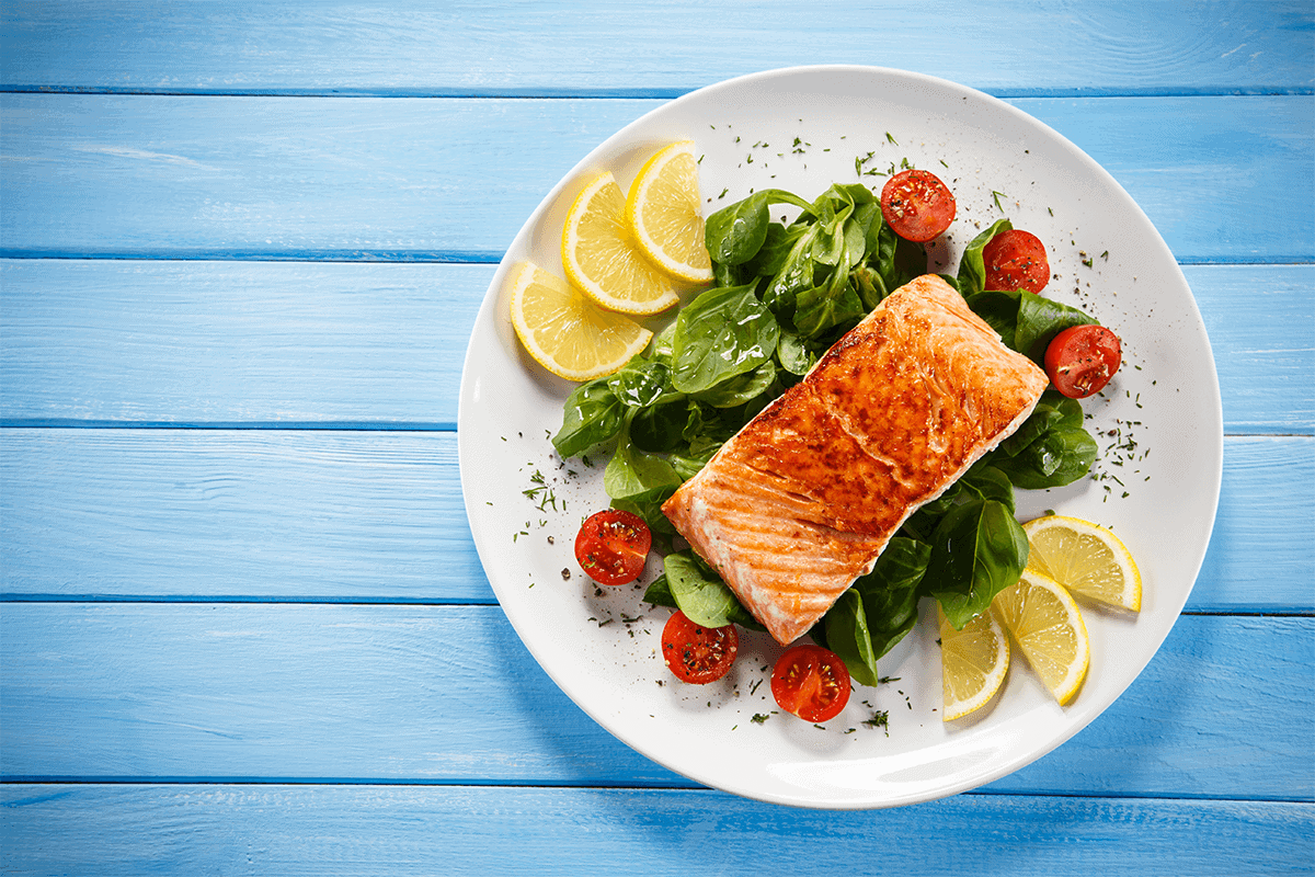 cooked salmon with tomatoes greens and lemon slices on a white plate placed on wooden blue table