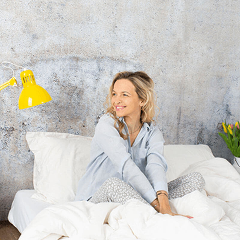 Women smiling while sitting in bed