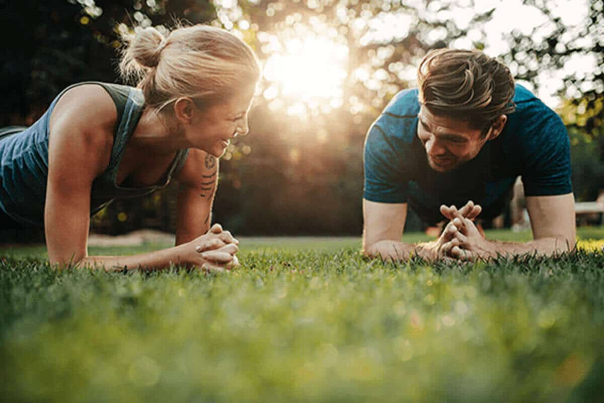 Man and woman planking outdoors on grass