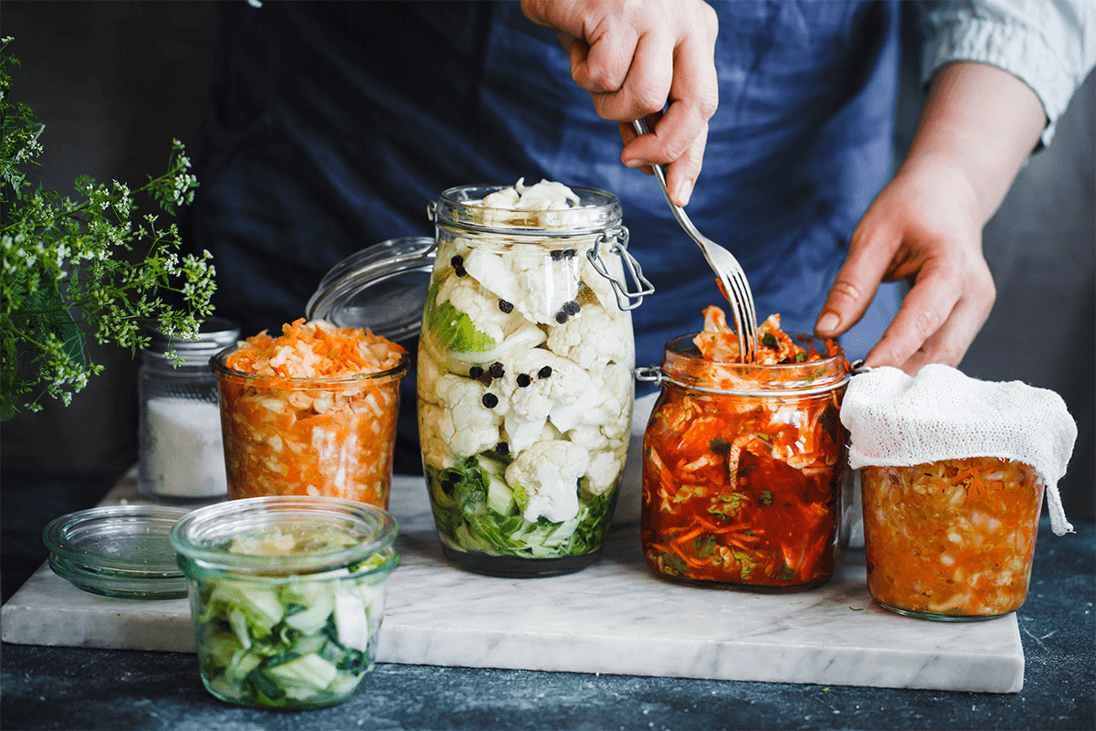 5 pickled ingredients in 5 glass jars with person stuffing one jar with fork