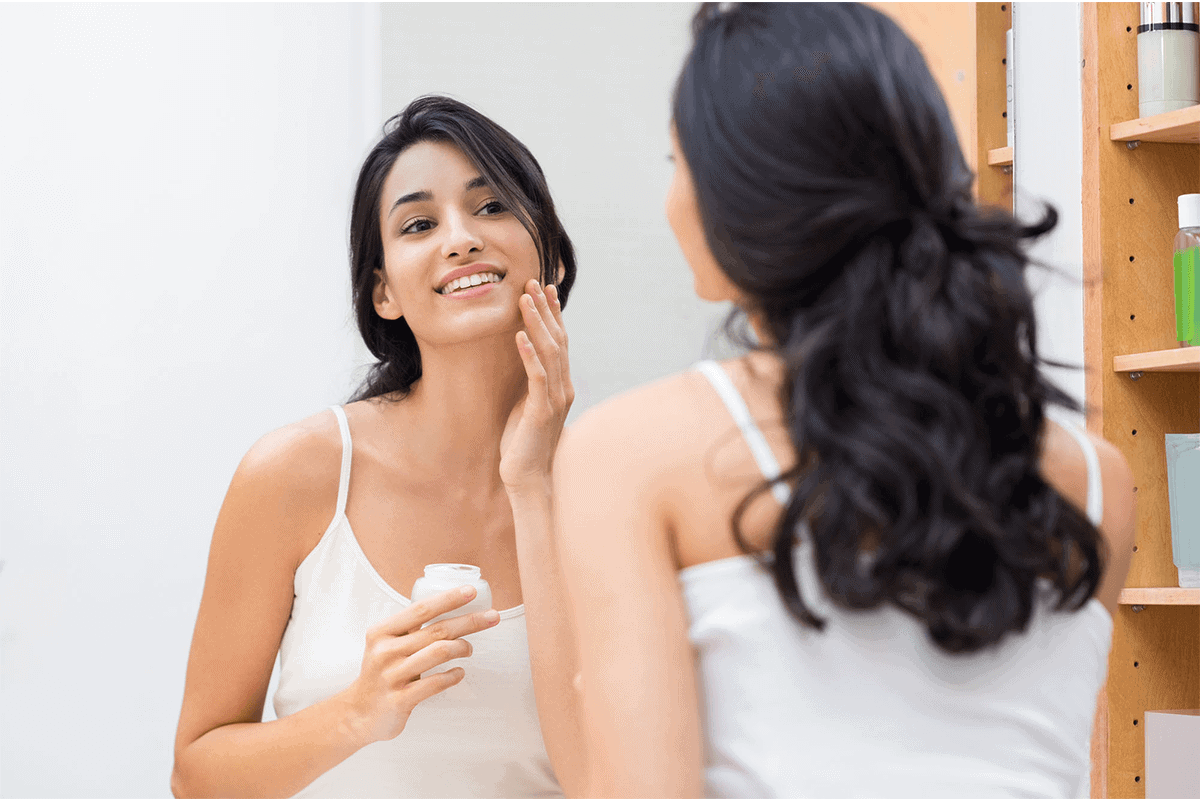 woman looking at herself in the mirror and applying moisturizer to her face