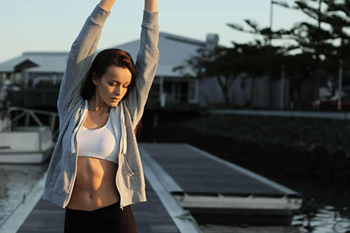 woman stretching with her hand in the air in active clothing outdoors