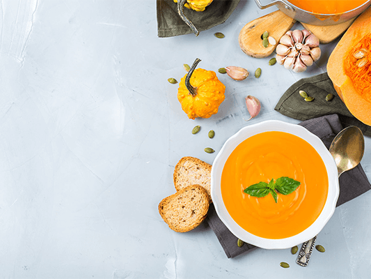 orange pumpkin soup with dried bread slices with pumpkin decoration on marble table