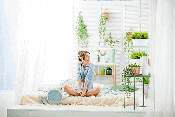 woman in her room cross-legged sitting on bed with green plants around her