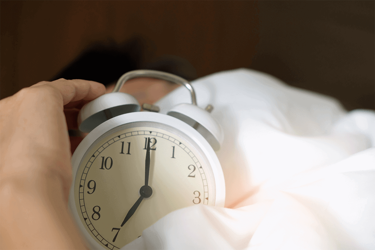 person in bed holding a white alarm clock