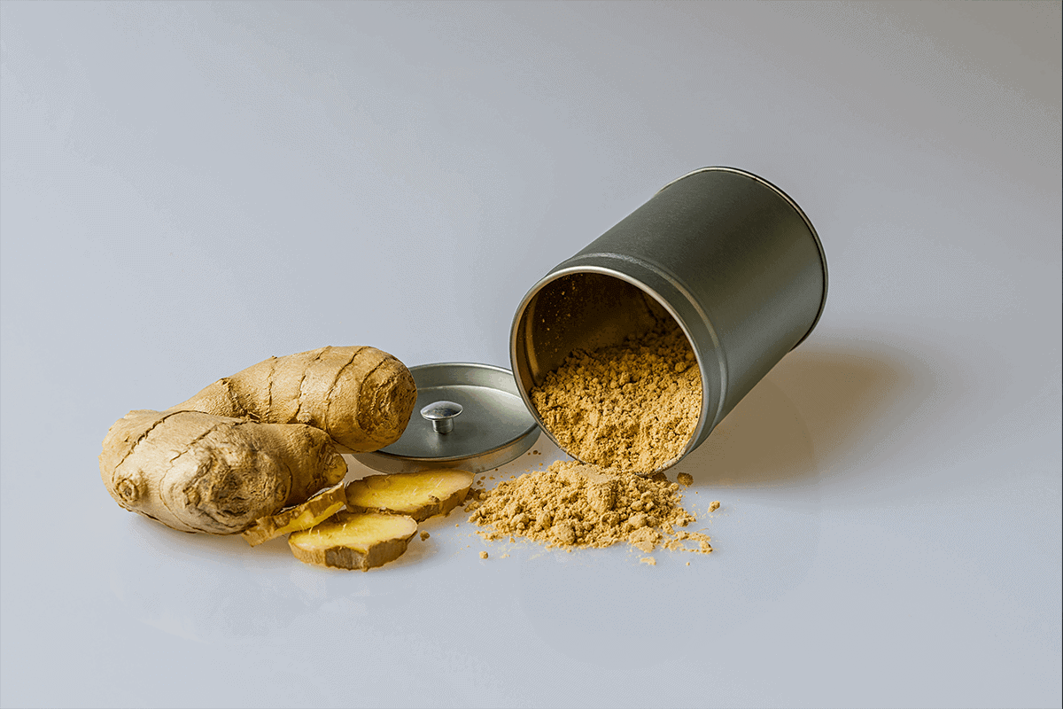 ginger and ginger powder in tin can spread on table