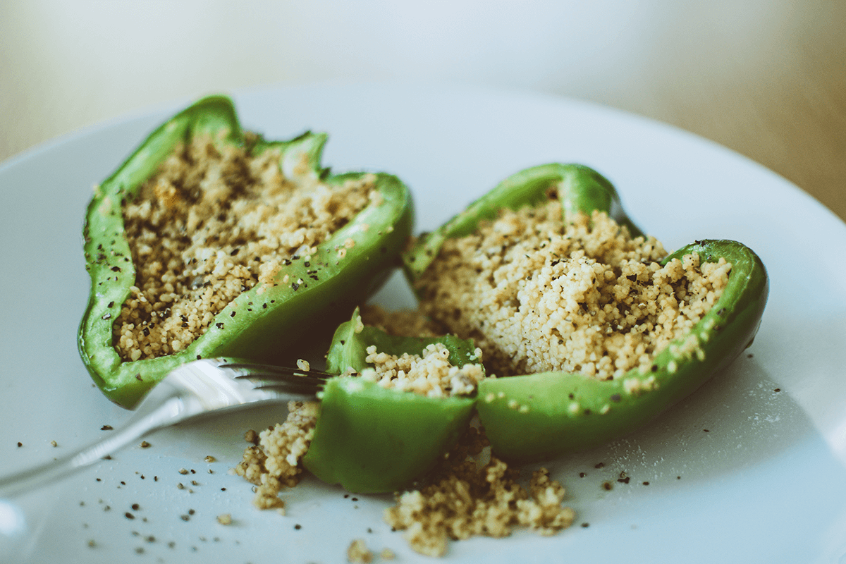 green pepper cut in half with quinoa inside on white plate with a fork