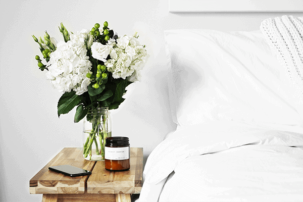 white bed with sheets, white flowers on a wooden bedside table