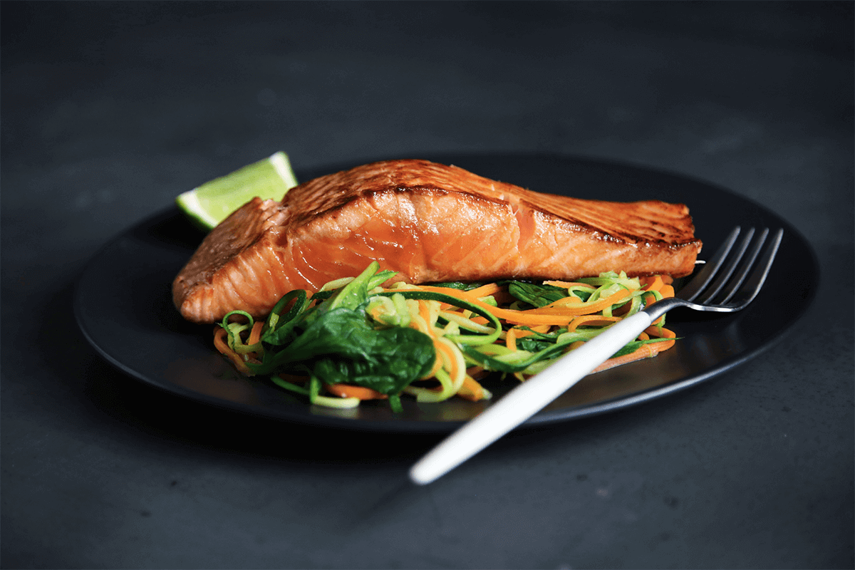 salmon and salad on a plate with a fork