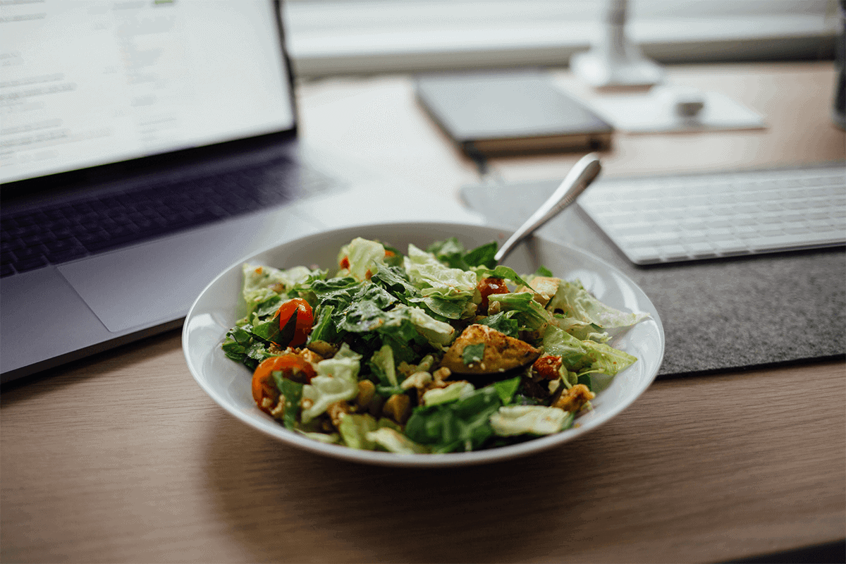 salad on desk next to laptop and keyboard