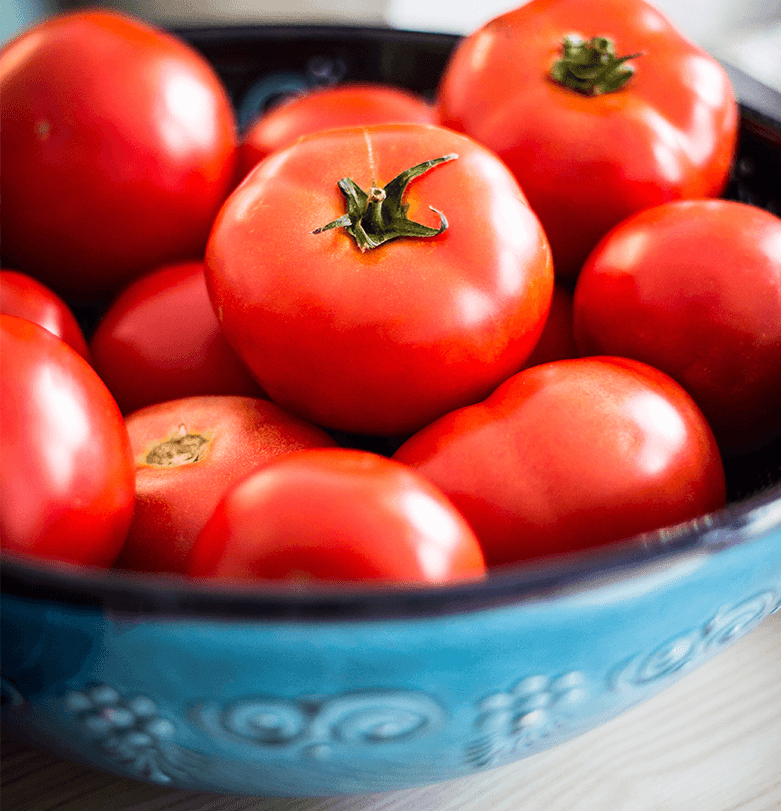 ripe red tomatoes in a blue bowl on a table