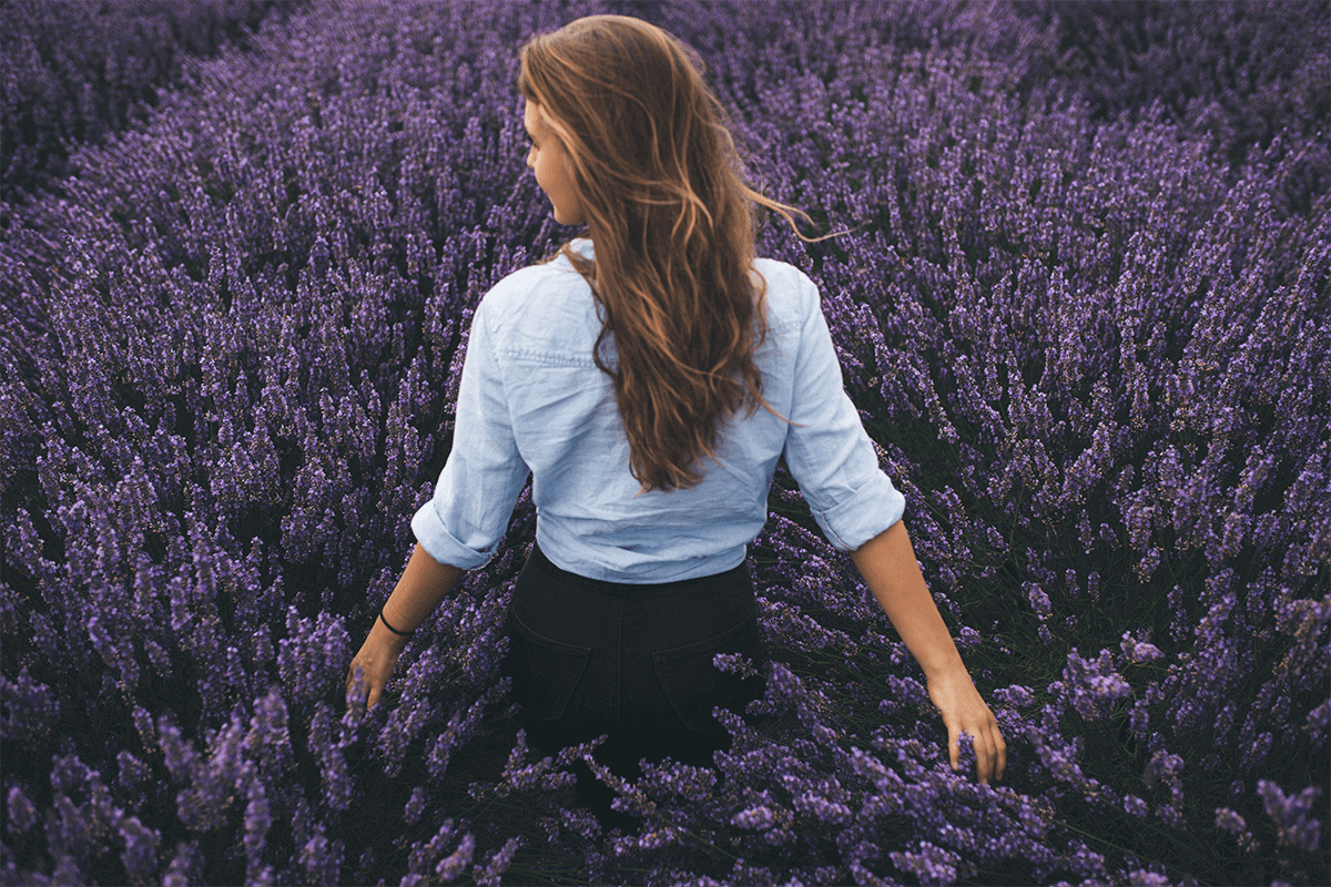 WOMAN WALKING IN FIELD OF LAVENDER