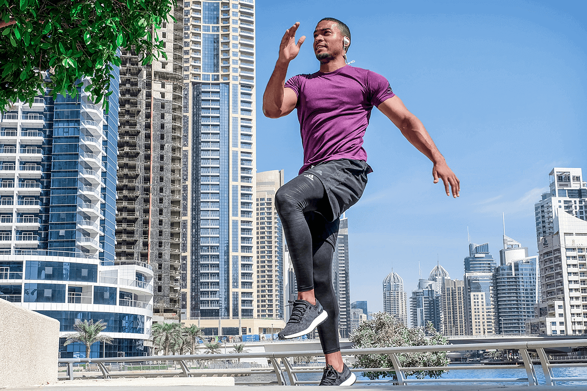 man exercising on the lake shore of a metropolitan with tall buildings in the background