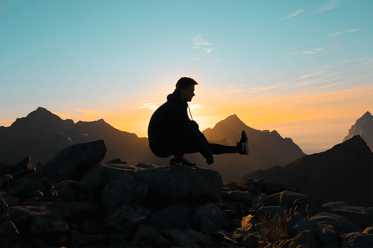 man crouching on one leg with the other leg extended on a rock in the mountains