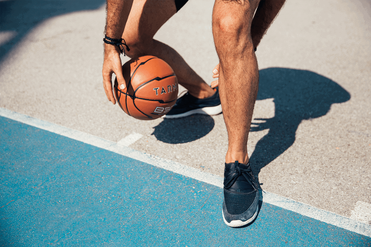 male dribbling basketball in between his legs