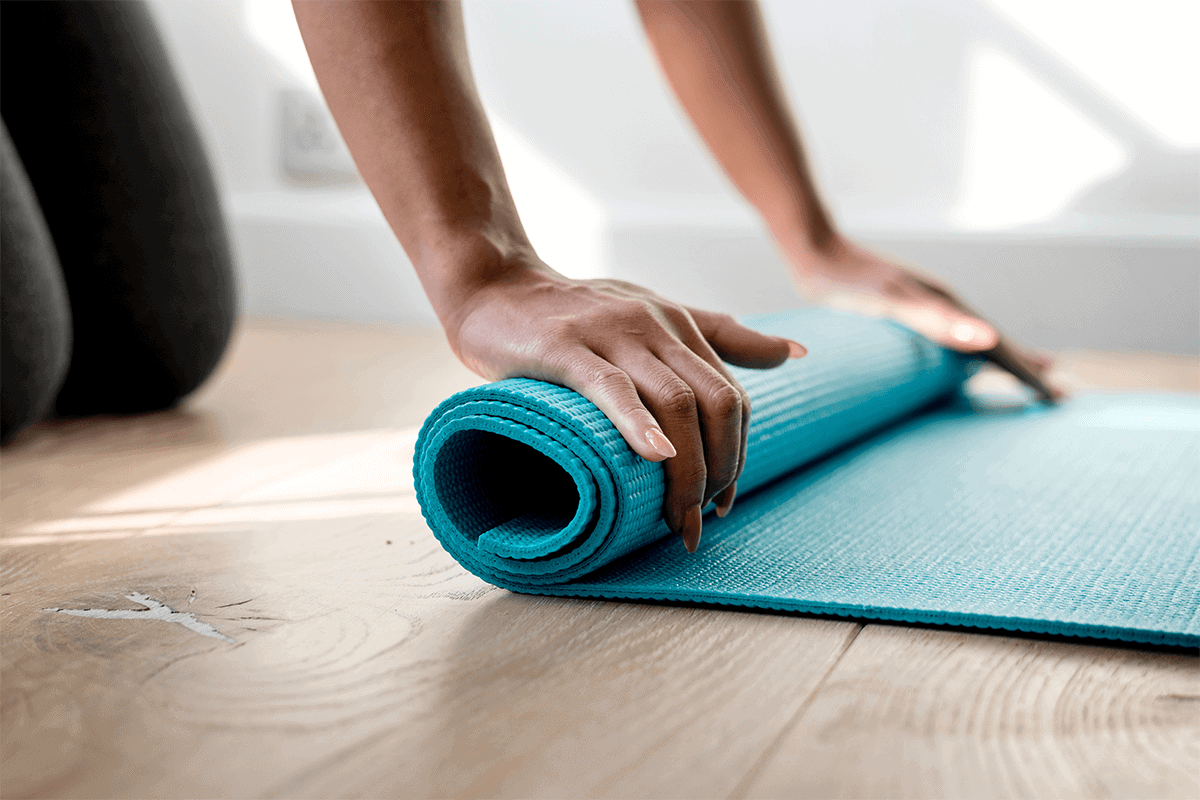 woman rolling her blue yoga mat