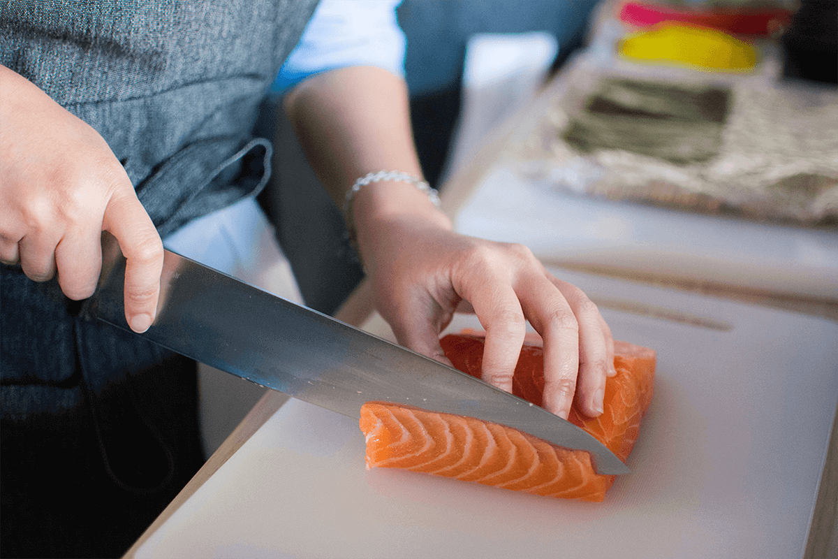 person cutting a piece of salmon into multiple pieces for cooking