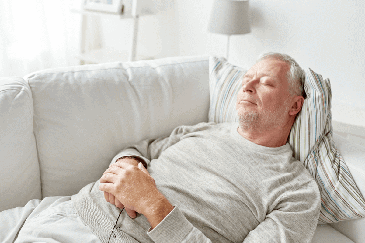 older man sleeping on a white couch