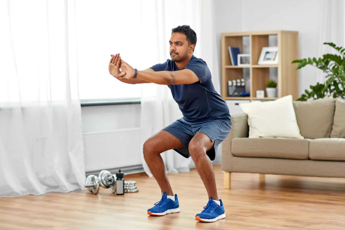 man squatting in living room