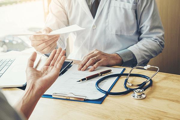 practitioner handing a patient a paper recommendation
