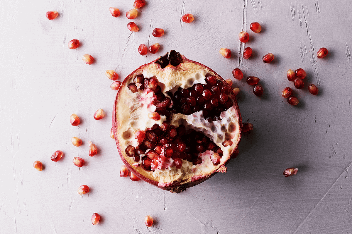 pomegranate with seeds around the fruit