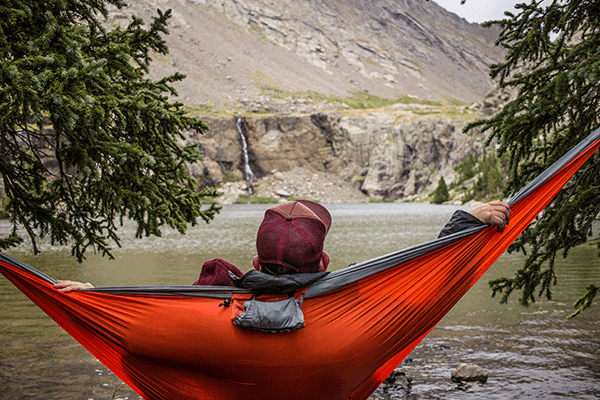 man laying in a hammock looking into the mountains outdoors
