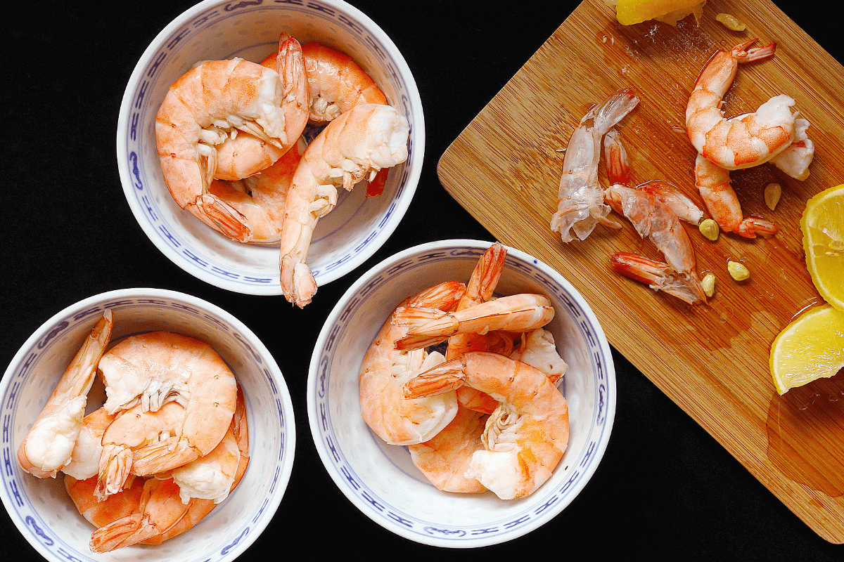 raw shrimp in three white bowls beside wooden cutting board with lemons