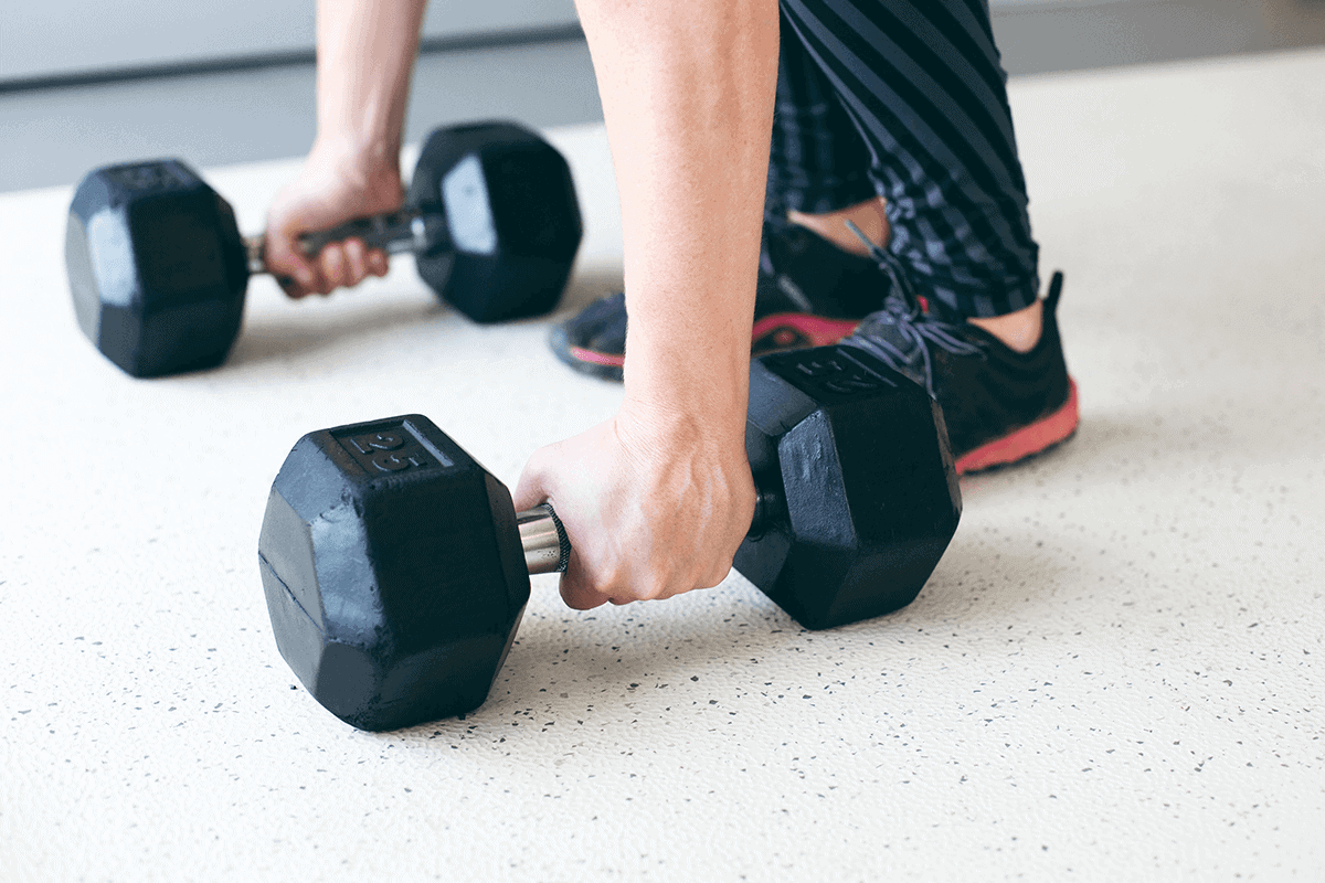 man lifting weights in both hands at gym