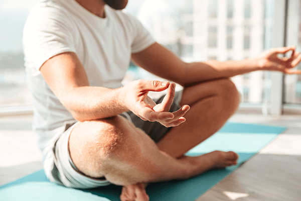 man meditating with buildings in the background