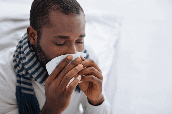 man with a scarf drinking a warm beverage from white mug sitting on bed