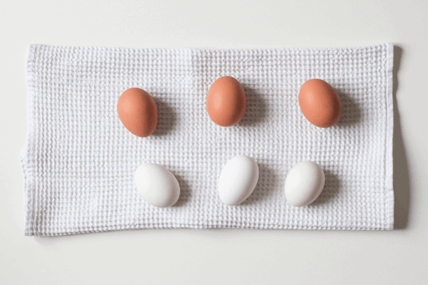 three brown eggs and three white eggs on a white cloth on a table