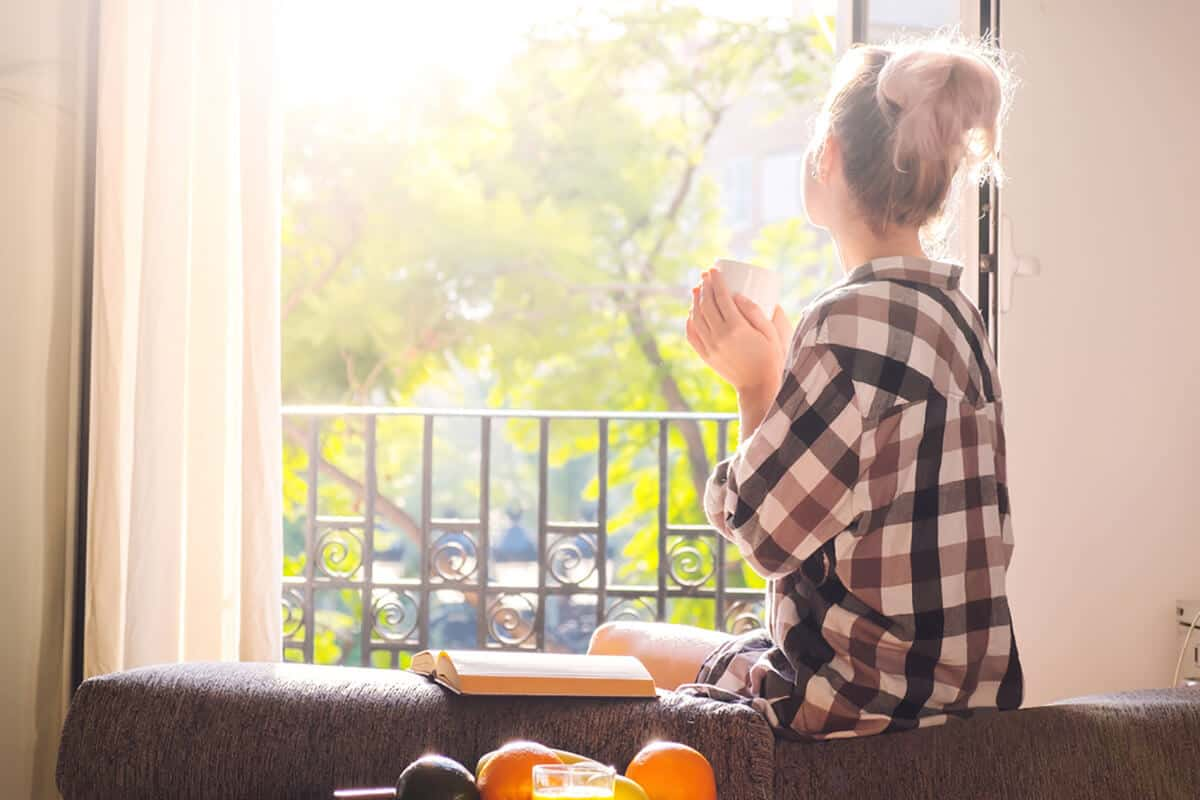 woman sitting on couch and looking out of her window as the sunny day with a mug in her hands