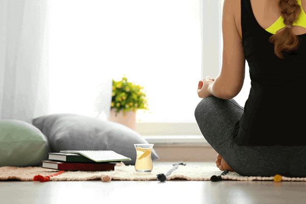woman sitting on yoga mat relaxing with a cup of tea next to her