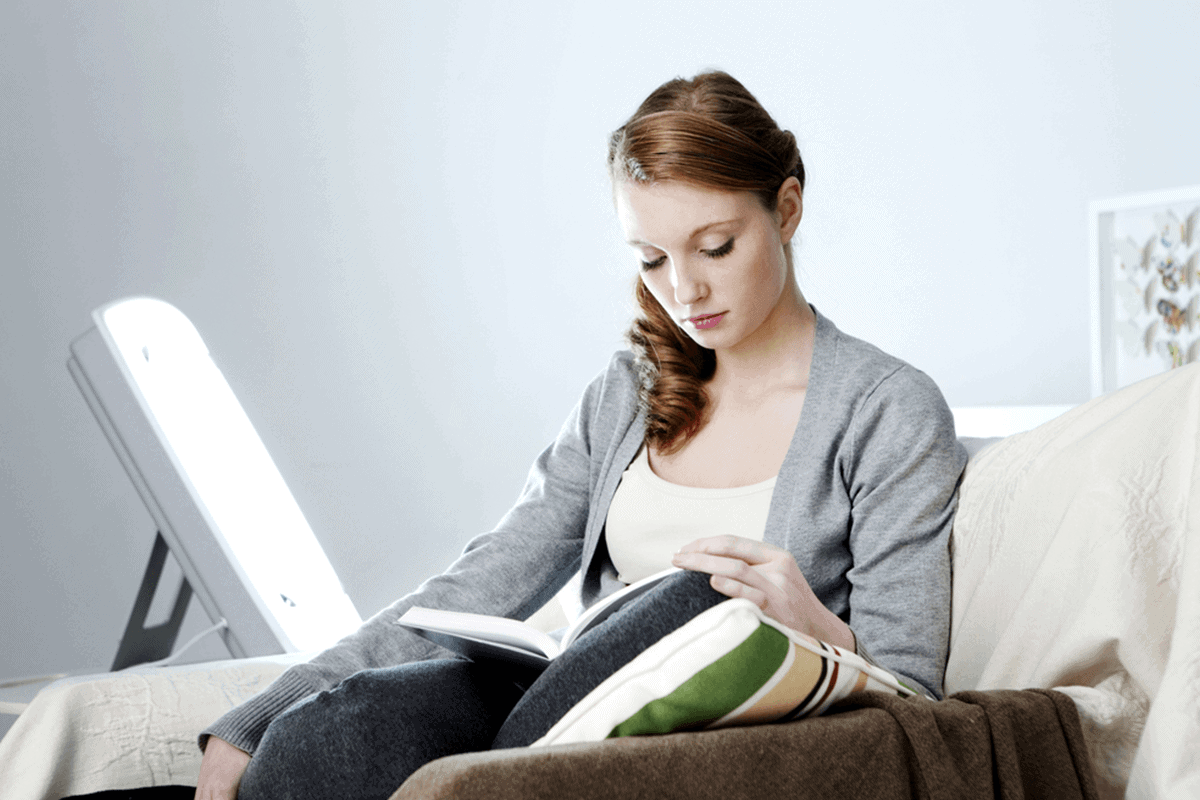 woman sitting on couch and reading a book with light therapy box next to her