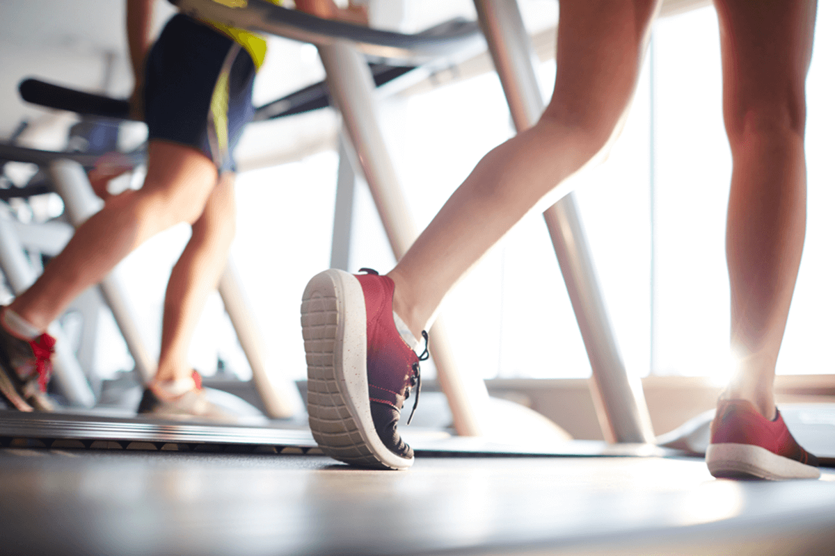 close up of two people's legs and feet running on treadmills in gym