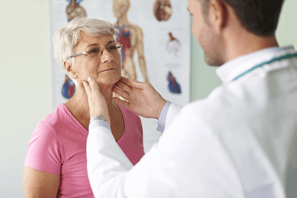 male doctor examining elderly woman's thyroid in doctor office