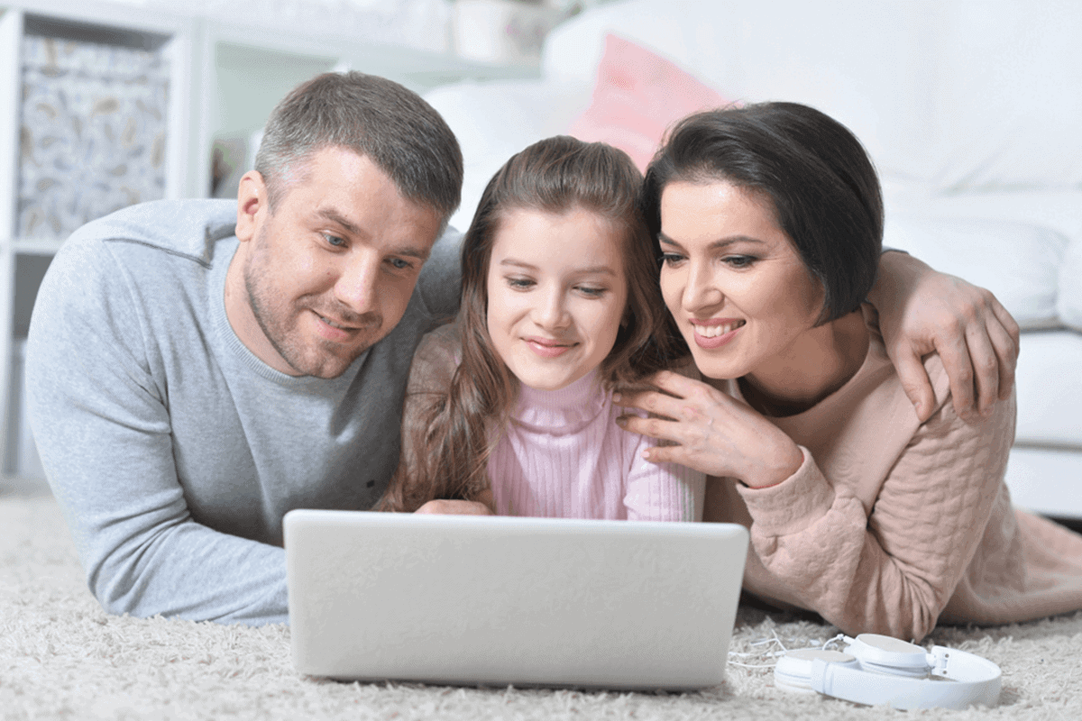 father, daughter, and mother watching something on laptop