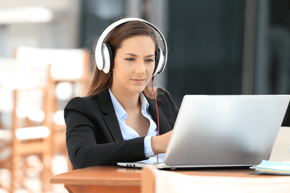 woman with headphones on looking at her laptop screen while sitting