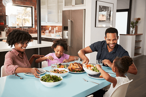 family of four sitting at dinner table and eating together