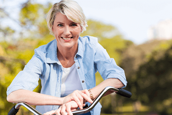 woman leaning on her bike smiling while outside