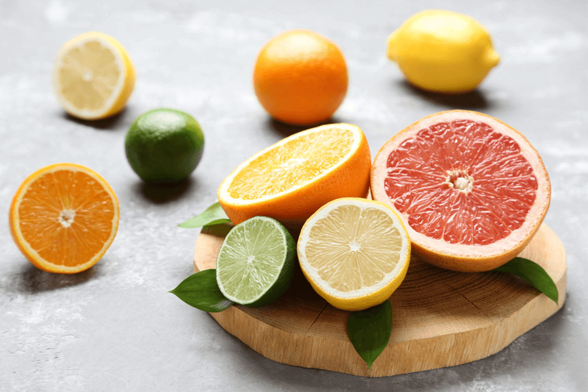 cut up limes, grapefruit, lemons, and oranges on a table