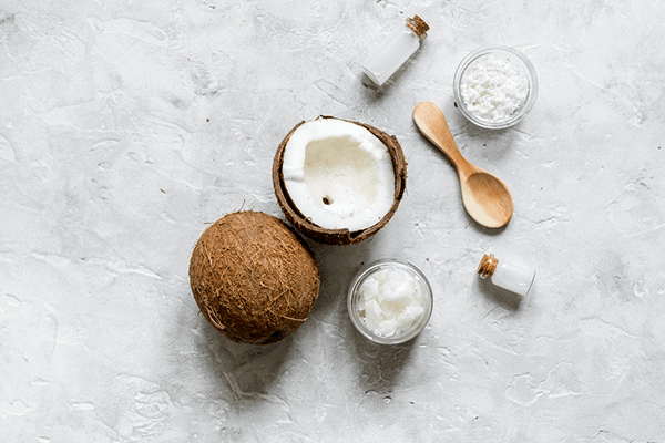whole coconut next to a half coconut surrounded by coconut extract in solid and liquid form
