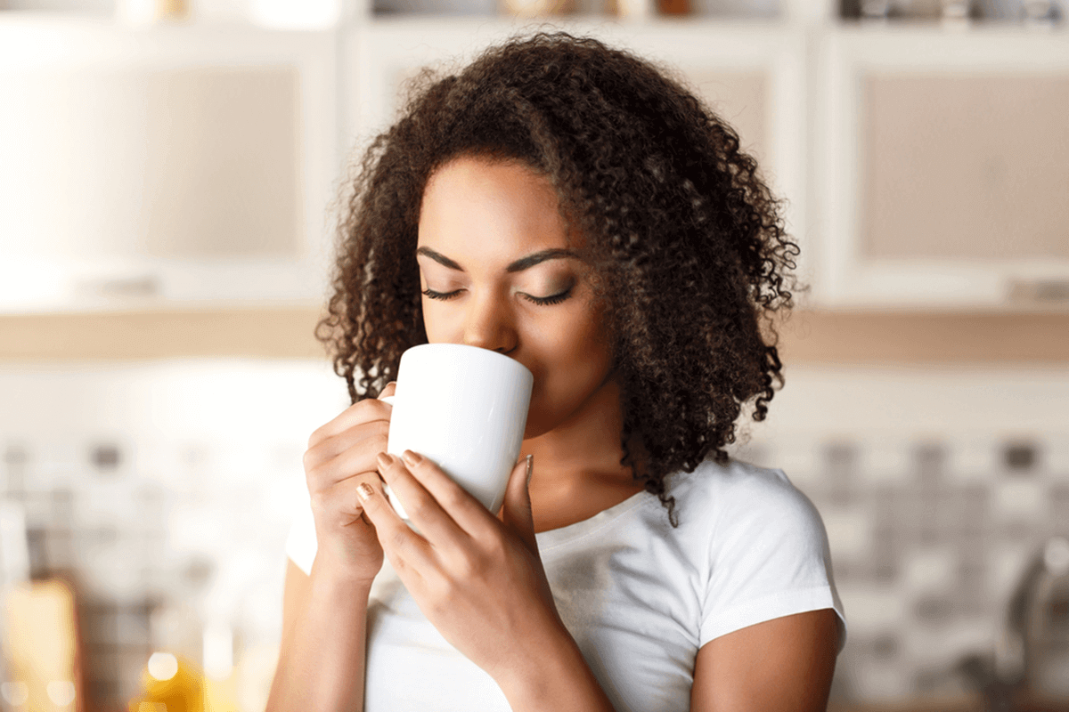 woman drinking a beverage in a white cup