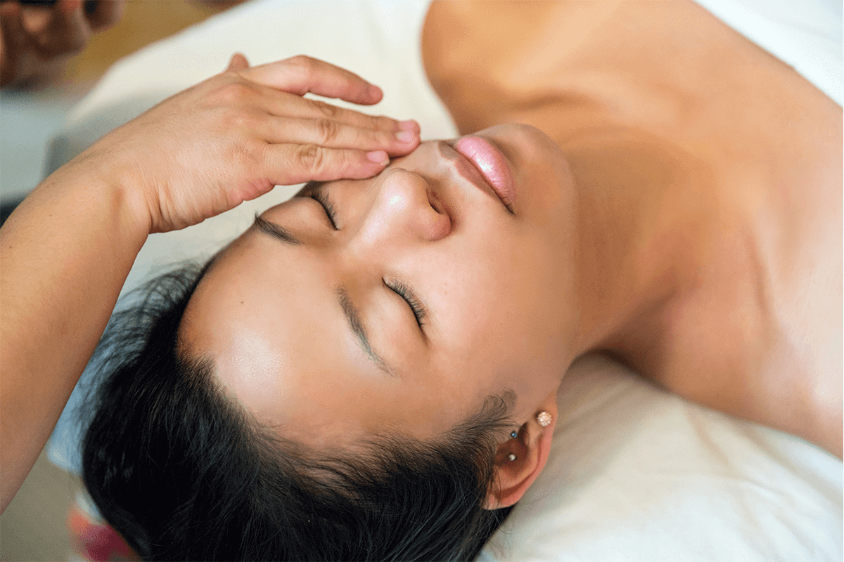 woman lying down and relaxing while getting a facial massage