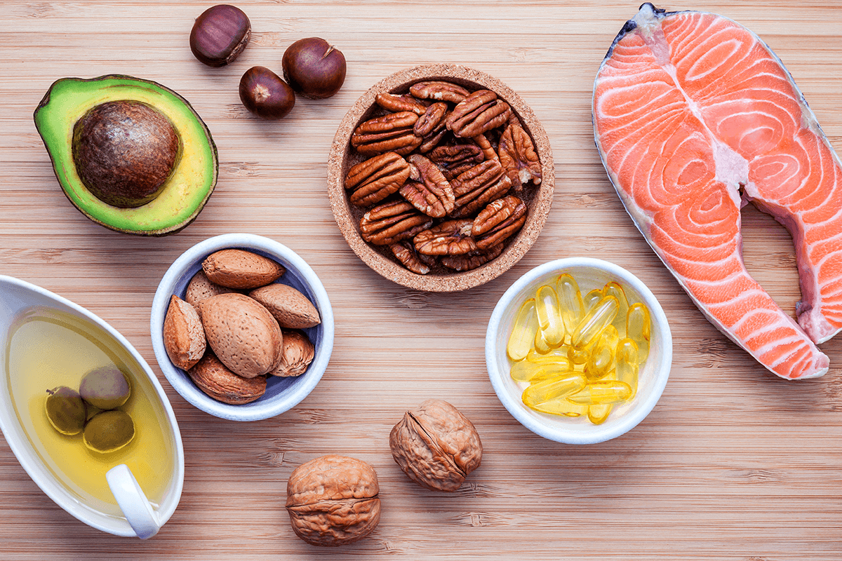 olive oil, avocado, walnuts, hazelnuts, fish, and supplements on wooden table
