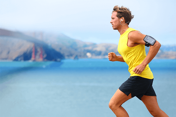 man running next to a body of water, outside