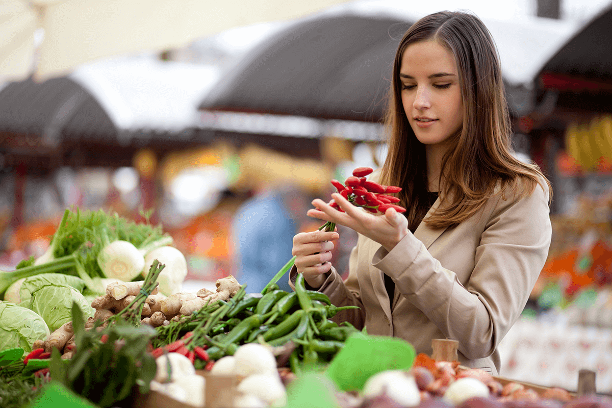 woman holding red chilly peppers in local food market